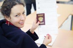 Женщина показывает пасспорт и голосуя бумагу Стоковая Фотография