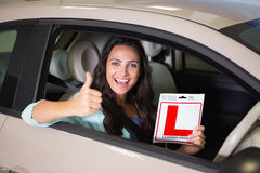 Женщина показывать большие пальцы руки вверх держа знак водителя учащийся стоковое изображение