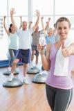 женщина показывать большие пальцы руки вверх при люди протягивая студию фитнеса рук Стоковое Изображение