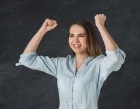 Женщина показывать при поднятые оружия, наслаждаясь успехом стоковое фото