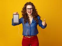 Женщина показывая большие пальцы руки вверх и слушая к музыке с наушниками Стоковое Фото