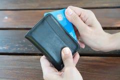 Женщина показывая держащ черный кожаный бумажник с карточкой банка на деревянном столе в Canakkale Турции 2017 Стоковые Фотографии RF