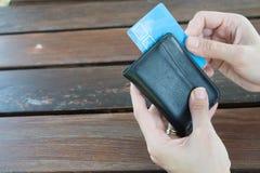 Женщина показывая держащ черный кожаный бумажник с карточкой банка на деревянном столе в Canakkale Турции 2017 Стоковое Фото