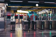 Женщина показывая ее билет к воротам машины и дефлектора на станции метро стоковое изображение