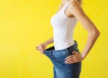 Женщина показывая ее большие брюки после успешной потери диеты и веса стоковая фотография rf