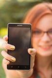 Женщина показывая ее умн-телефон Стоковая Фотография