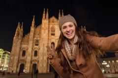 Женщина показывая жест победы и принимая selfie около Duomo стоковое изображение rf