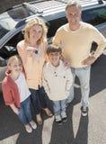 Женщина показывая ключи пока стоящ с семьей против автомобиля стоковые фото