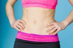 Женщина показывая некоторые сильный abs и плоский живот стоковые фото