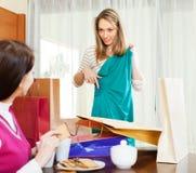 Женщина показывая новое зеленое платье к подруге Стоковое Изображение RF