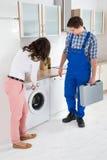Женщина показывая повреждение в стиральной машине к ремонтнику Стоковое Фото