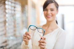 Женщина показывая стекла на магазине стоковое изображение rf