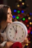 Женщина показывая часы перед светами рождества Стоковое Изображение
