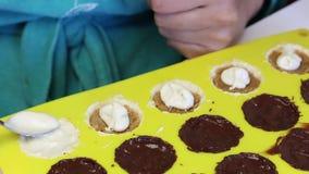 Женщина покрывает расплавленный шоколад заполняя с задавленной миндалиной, которая в форме силикона Варящ конфеты застекленные в  видеоматериал