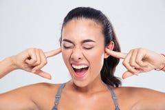 Женщина покрывая ее уши с пальцами и кричать Стоковая Фотография