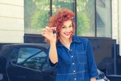 Женщина, покупатель около ее нового показа автомобиля давая ключи стоковое фото rf