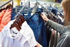Женщина покупателя выбирает одежды джинсов в магазине Стоковое фото RF