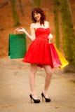 Женщина покупателя осени с продажей кладет внешнее в мешки в парке Стоковые Фото
