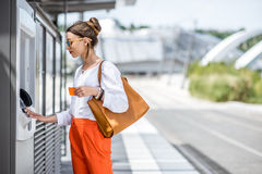 Женщина покупая билет или используя ATM outdoors стоковые изображения rf