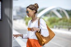 Женщина покупая билет или используя ATM outdoors стоковое изображение