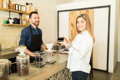 Женщина покупая некоторый кофе на магазине Стоковые Фото