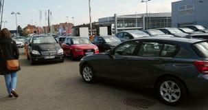 Женщина покупая новую МИНУТУ, Мерседес-Benz, автомобиль Audi на торговце