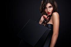 Женщина покупок держа серую сумку изолированный на темной предпосылке в черном празднике пятницы Стоковая Фотография RF