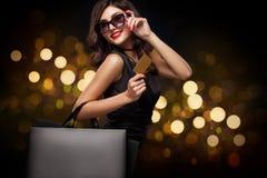 Женщина покупок держа серую сумку на предпосылке Нового Года с bokeh светов в черном празднике пятницы стоковая фотография