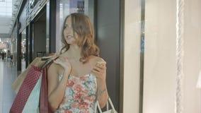 Женщина покупок посылая текстовое сообщение на ее сотовом телефоне акции видеоматериалы
