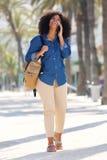Женщина полного тела усмехаясь идя и говоря снаружи на мобильном телефоне Стоковое Изображение RF