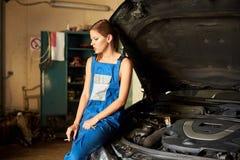Женщина положилась против открытого клобука автомобиля в гараже стоковое фото rf