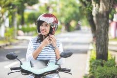 Женщина положила ее шлем дальше перед ехать мотоцилк стоковое изображение rf