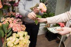 Женщина получает оплату для букета в магазине цветка стоковая фотография rf