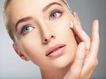 Женщина получает сливк в стороне Принципиальная схема внимательности кожи Стоковые Фото