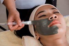 женщина получая ее предусматрива стороны с маской грязи стоковое фото