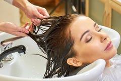 Женщина получая ей волосы помытый стоковая фотография