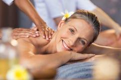 Женщина получая массаж масла на курорте Стоковые Изображения