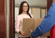 Женщина получая пакет от курьера обслуживания доставки стоковые изображения