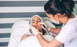 Женщина получая rf поднимаясь в ее сторону в клинике стоковое изображение rf