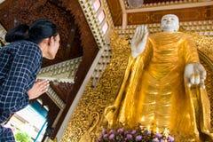 Женщина помоленная на большом золотом Будде стоковые фотографии rf