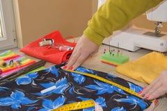 Женщина портноя работая в его магазине портноя Портной работая на студии Рука ` s женщины шьет ткань handmade руки женщины needl Стоковая Фотография