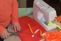 Женщина портноя работая в его магазине портноя, портняжничая Женский портной продевая нитку кожаный материал на швейной машине Стоковое Изображение