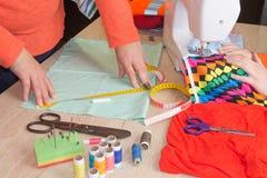 Женщина портноя работая в его магазине портноя, портняжничая Женский портной продевая нитку кожаный материал на швейной машине Стоковые Фотографии RF