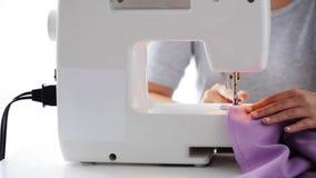 Женщина портноя с тканью швейной машины шить