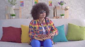 Женщина портрета Афро-американская с афро стилем причесок визуально повредила чтение книги с вашими пальцами сток-видео