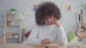Женщина портрета Афро-американская с афро стилем причесок читая книгу на таблице акции видеоматериалы
