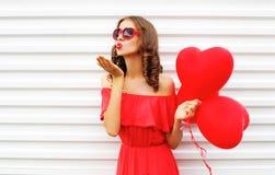 Женщина портрета в красном платье посылает поцелуй воздуха с формой сердца воздушного шара над белизной Стоковое Фото