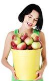 Женщина портрета держа ведро полный яблок Стоковая Фотография