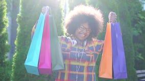 Женщина портрета жизнерадостная африканская с афро стилем причесок с пакетами после ходить по магазинам смотрящ камеру медленный  акции видеоматериалы