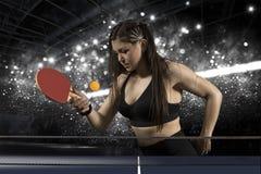 Женщина портрета играя теннис на черноте стоковое фото